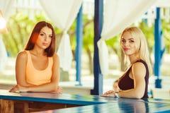 Två flickavänner som har roligt utomhus- i sommar Kvinnan väntar på deras coctailar Arkivbild