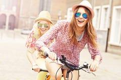 Två flickavänner som rider den tandema cykeln royaltyfria foton