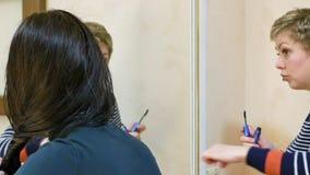 Två flickavänner som skvallrar i dressingmakeuprum arkivfilmer