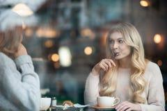 Två flickavänner som trinking kaffe i kafét och tillsammans spenderar tid Arkivfoto