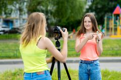 Två flickavänner, sommar i natur Antecknar en video om smartphonen I handhållna telefonen Leenden lyckligt royaltyfria bilder