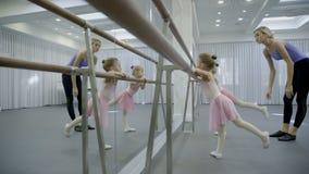 Två flickor är övning nära barren med lagledaren i balettstudio lager videofilmer