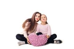 Två flickor är sitta och rymma en kudde i deras händer Royaltyfri Fotografi