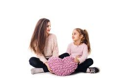 Två flickor är sitta och rymma en kudde i deras händer Fotografering för Bildbyråer