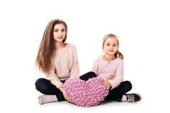 Två flickor är sitta och rymma en kudde i form av en hjärta Royaltyfria Bilder