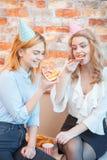 Två flickor äter pizza i ett kontorsrum royaltyfri bild