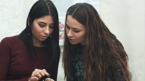 Två flickor använder en smartphone och att tala, att le som sitter på soffan arkivfilmer