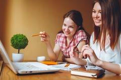 Två flickor arbetar på kontoret på datoren och minnestavlan royaltyfri foto