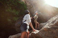 Två flickor av en turist- flickvän för ` s klättrar bergen, hjälper sig, når ut en portionhand arkivfoto