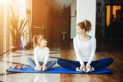 Två flickor av olika åldrar som gör yoga Royaltyfria Bilder