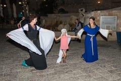 Två flickor - av riddarna av den Jerusalem klubban, iklädda traditionella dräkter av medeltida damer, dans med en flicka på natte Arkivfoto