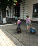 Två flickor av systern går med påsar till stationen royaltyfri bild