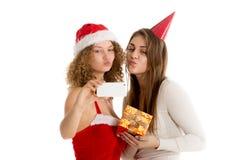 Två flickor blåser en kyss, medan ta selfie i cristmasdräkter Arkivbilder