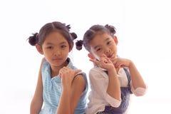 Två flickor drar tillbaka tillsammans på whaitebakgrund Arkivbild