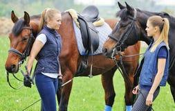 Två flickor - dressyrryttare med hästar Arkivbild