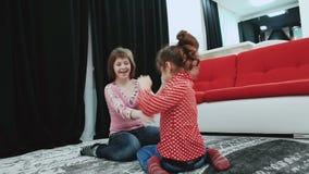 Två flickor, ett av dem med Down Syndrome som hemma sitter på mattan, lek och, har gyckel stock video