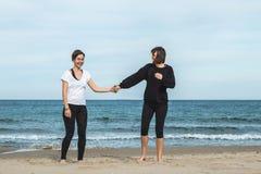 Två flickor fångade innehavhänder på stranden fotografering för bildbyråer