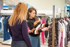 Två flickor går att shoppa, väljer kläder i lagret arkivbilder