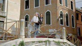 Två flickor går i Venedig Flickvänner imponeras av den berömda staden Turism i Europa V?r arkivfilmer