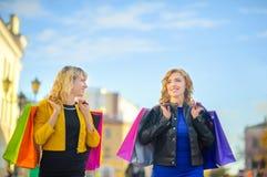 två flickor går och ler ner gatan med shoppingpåsar royaltyfri foto