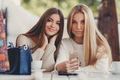 Två flickor håller ögonen på foto på smartphonen arkivfoto