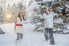 Två flickor har gyckel som kastar snö Royaltyfria Foton