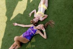 Två flickor i baddräkt har gyckel på gräset vid pölen Royaltyfri Bild