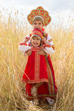 Två flickor i de ryska nationella sundressesna royaltyfri foto