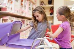 Två flickor i ett leksaklager med dockor ser in i barnvagnen royaltyfri foto