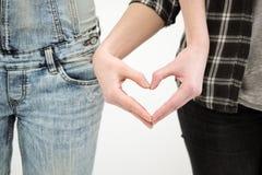 Två flickor i jeans rymmer händer stänger sig upp Vit bakgrund Homosexuella lesbiska par royaltyfri foto