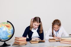 Två flickor i klassrumet lär kursböcker på hennes skrivbordjordklot arkivfoton