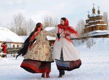 Två flickor i nationella dräkter som framme dansar i fyrkanten av en träkyrka i snön under traditionellt arkivfoton