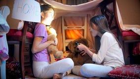 Två flickor i pyjamas som skrämmer sig i tält på sovrummet royaltyfri fotografi