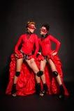 Två flickor i röda klänningar Fotografering för Bildbyråer