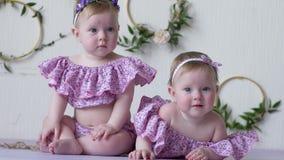 Två flickor i rosa dräkter poserar på photoshoot på bakgrund av väggen med dekoren arkivfilmer