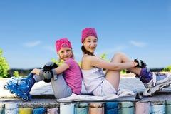 Två flickor i rullskridskor som sitter sidan - förbi - sid på gatan Arkivfoton