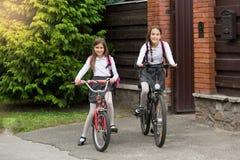 Två flickor i skolalikformig med påsar som rider till skolan på bicycl Royaltyfria Bilder