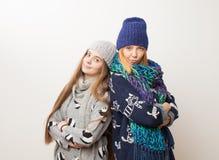 Två flickor i vinter beklär anseende bredvid vit bakgrund arkivfoto