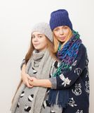 Två flickor i vinter beklär att krama på vit bakgrund fotografering för bildbyråer