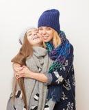 Två flickor i vinter beklär att krama på vit bakgrund royaltyfri foto