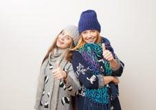 Två flickor i vinter beklär att skratta på vit bakgrund arkivbild