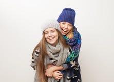Två flickor i vinter beklär att skratta på vit bakgrund Royaltyfri Foto