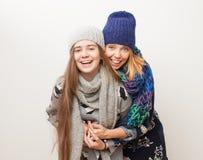 Två flickor i vinter beklär att skratta på vit bakgrund Arkivbilder