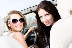 Två flickor kör bilen arkivfoto
