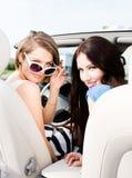 Två flickor kör cabrioleten royaltyfri foto