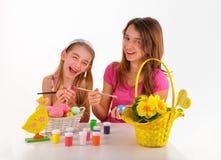 Två flickor, korg med kulöra ägg, målar för att färga och en vase av blommor Arkivfoto