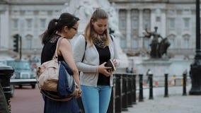 Två flickor läste en lopphandbok i centret av London arkivfilmer
