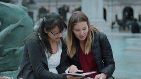 Två flickor läste en lopphandbok i centret av London stock video