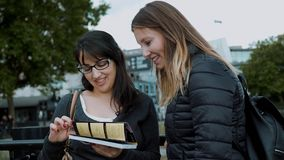 Två flickor läste en lopphandbok i centret av London lager videofilmer
