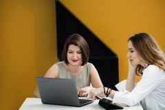 Två flickor med bärbara datorn på tabellen Royaltyfri Foto